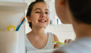 Young girl from Carlsbad looking her self in the mirror, and brushing her teeth